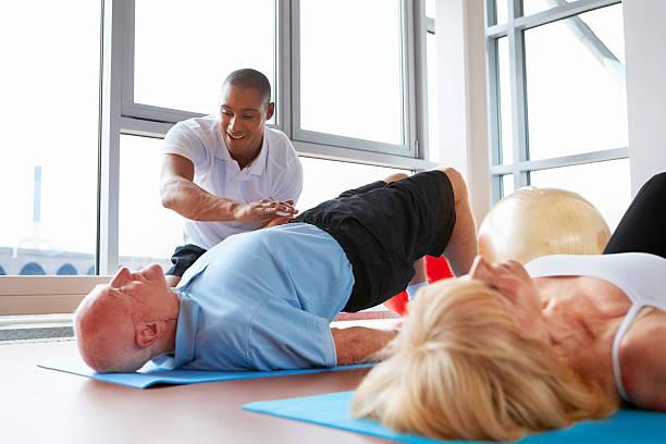 Aktive Senioren Dehnung im Fitnessraum mit persönlichem trainer – Foto