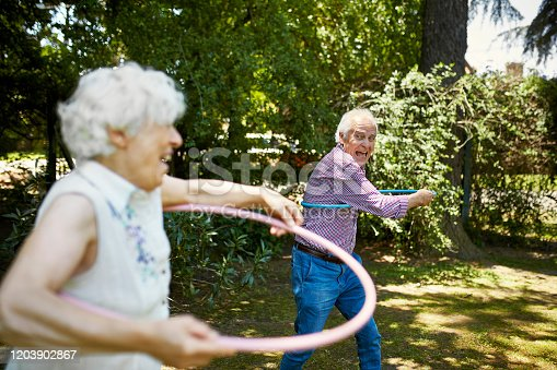 Close-up of fun-loving senior Hispanic couple in 60s and 70s swinging plastic toy hoops in sunny backyard.