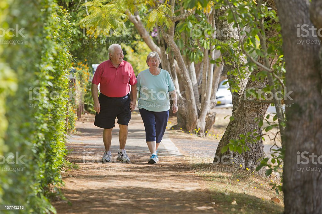 Active Seniors Walking and Holding Hands stock photo