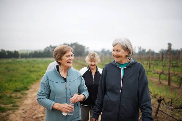 Active seniors women walking for exercise outdoors talking together waist up stock photo