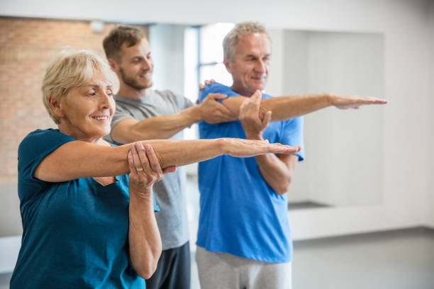 Active seniors working out with trainer stock photo
