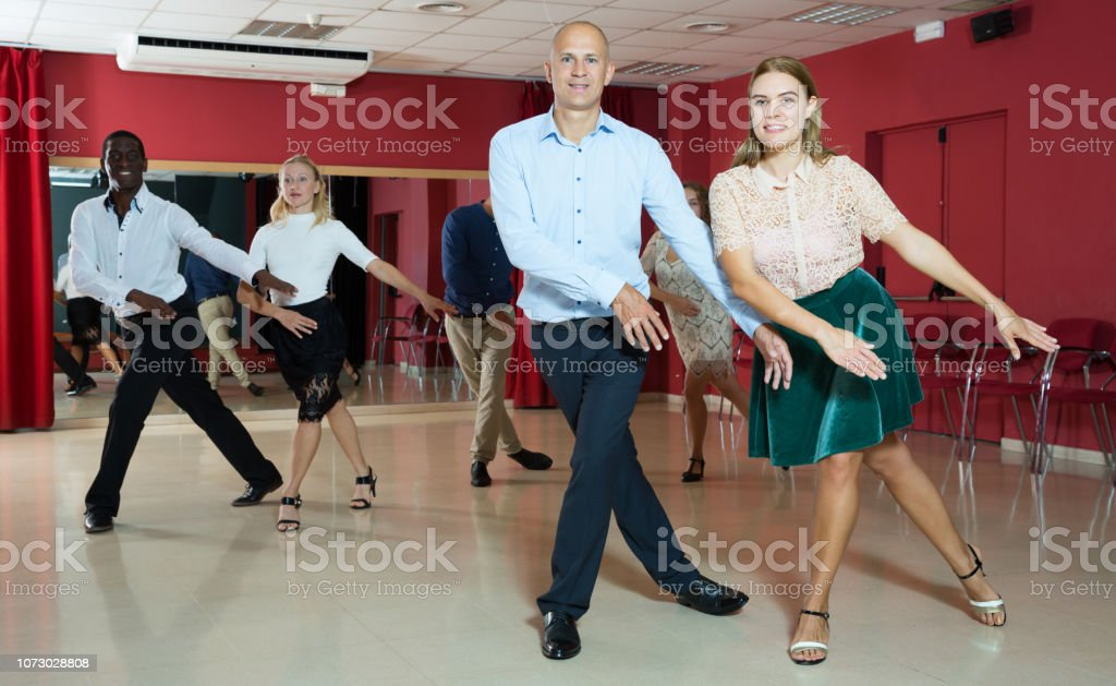 Young active smiling people practicing lindy hop movements in dance...