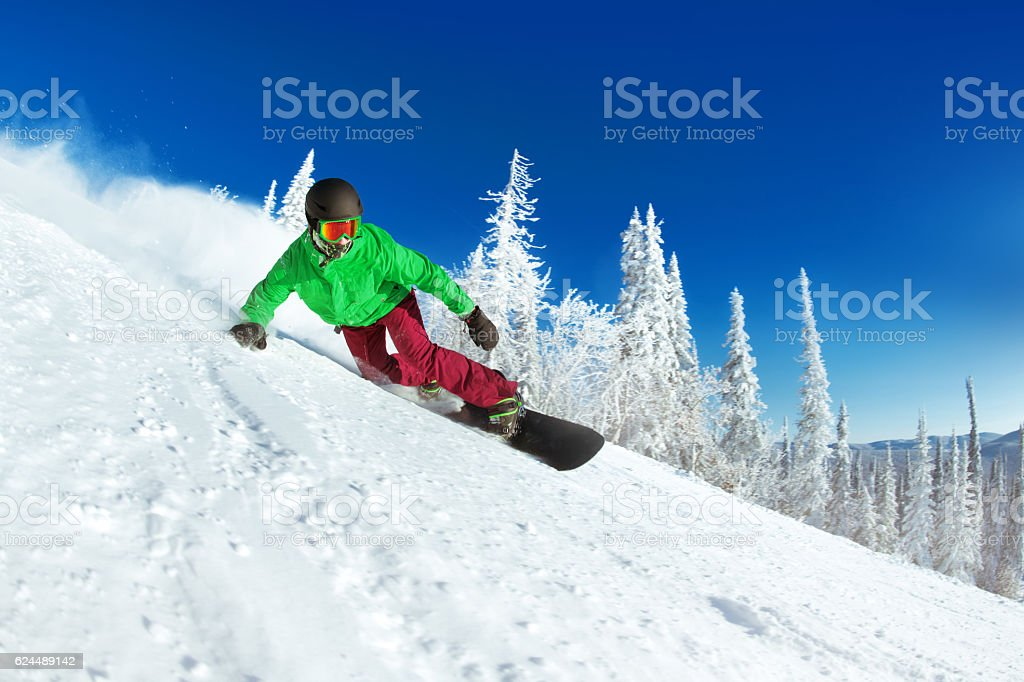 Active snowboarder snowboarding rides closeup stock photo
