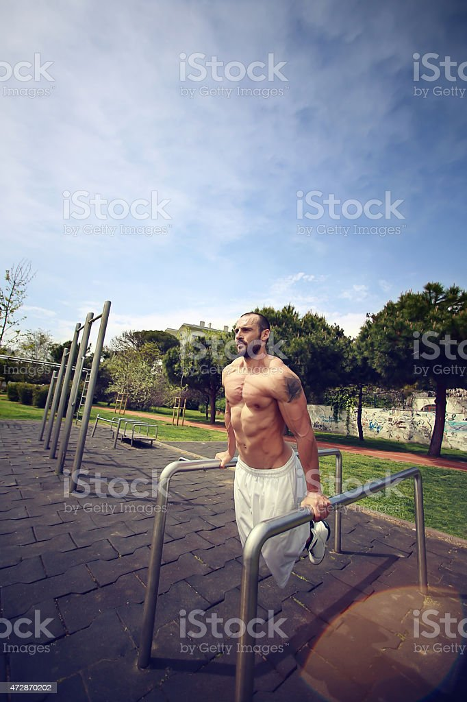 Active sports man doing parallel bar dips in -stock image stock photo
