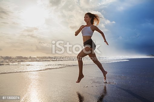 638628530 istock photo Active sporty woman run along sunset ocean beach. Sports background. 611300074