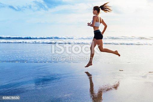 638628530 istock photo Active sporty woman run along sunset ocean beach. Sports background. 638628530