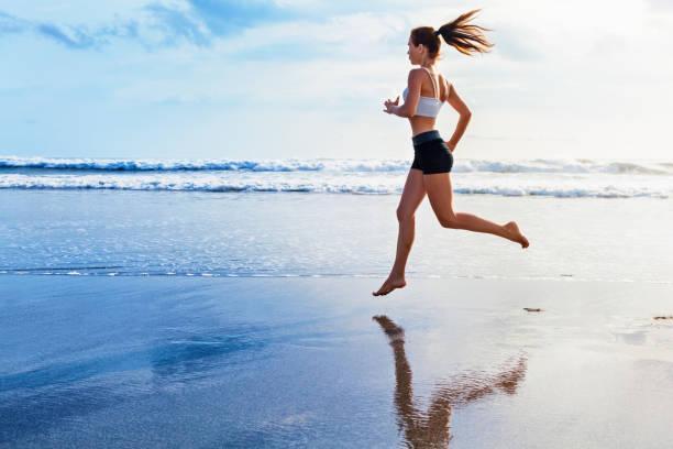 Active sporty woman run along sunset ocean beach. Sports background. stock photo
