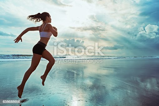 istock Active sporty woman run along sunset ocean beach. Sports background. 638688656