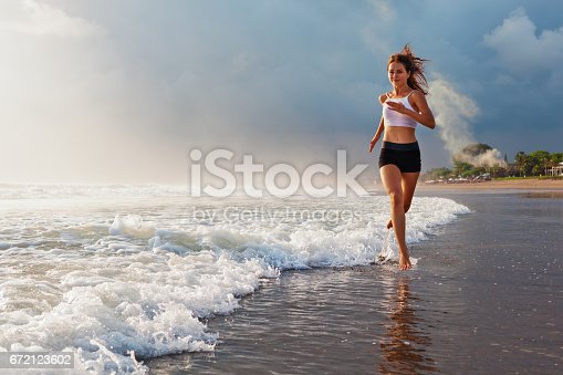 istock Active sporty woman run along sunset ocean beach. Sports background. 672123602