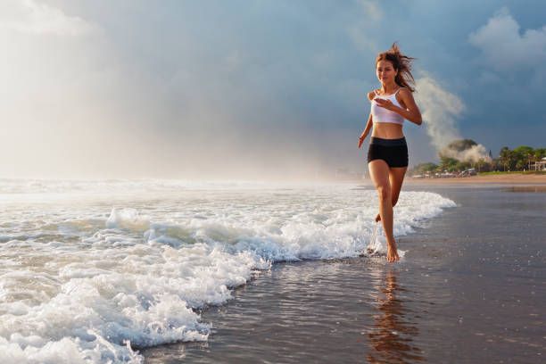 Active sporty woman run along sunset ocean beach. Sports background. stock photo