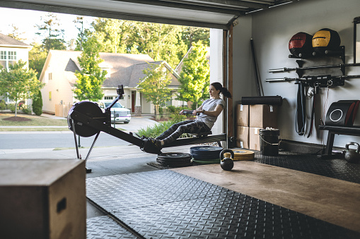 Photo of an active woman is exercising on a rowing machine in the home garage gym during covid-19 pandemic. Woman performing powerful pulls and focusing on endurance and cardio improvement.