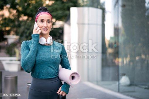 1091470492 istock photo Active woman in sports clothing talking on a mobile phone while standing in a city street 1091469244