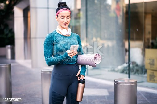 1091470492 istock photo Active woman in sports clothing using her mobile phone while standing in a city street 1082373872