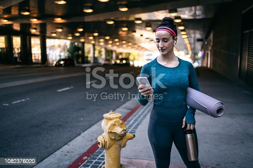 1091470492 istock photo Active woman in sports clothing using her mobile phone while standing in a city street 1082376020