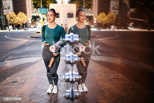 1091470492 istock photo Active woman leaning on a marble building wall while listening to music on wireless earbuds on a street sidewalk 1082375856