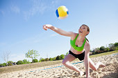 Athletic Caucasian woman reaches to hit a volleyball during volleyball game.
