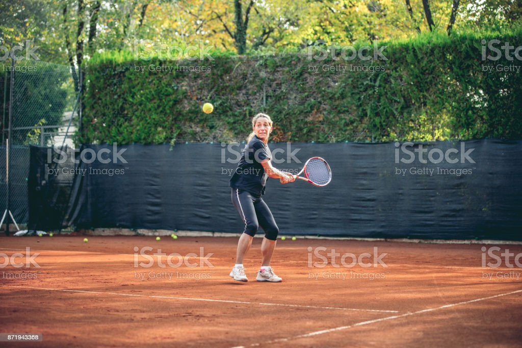 Active Woman Playing Tennis In Outdoor Tennis Court stock photo