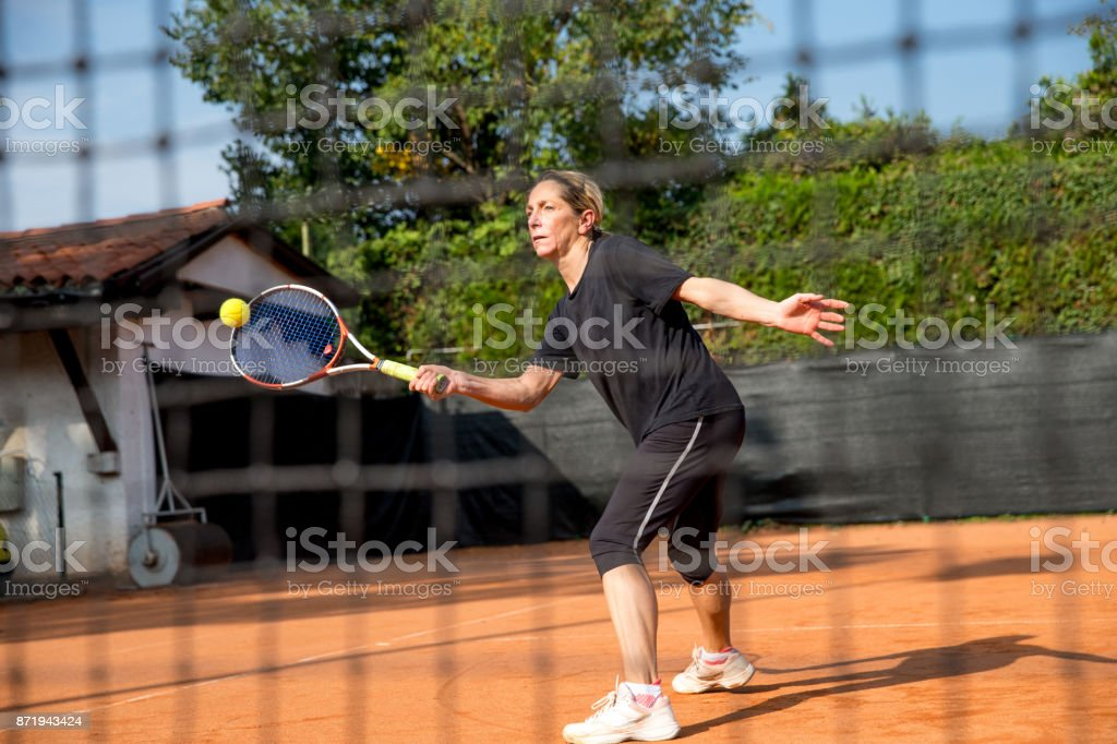 Active Woman Practicing Tennis Outdoors stock photo