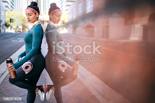 1091470492 istock photo Active woman resting while leaning on a marble building wall in a city centre 1082374028