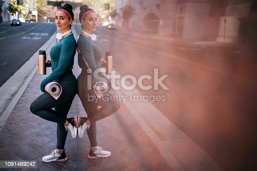 1091470492 istock photo Active woman resting while leaning on a marble building wall in a city center 1091469242