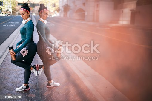 1091470492 istock photo Active woman resting while leaning on a marble building wall in a city center 1125598278