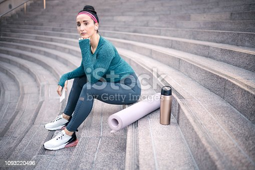 1091470492 istock photo Active woman sitting on the stairs in a downtown urban area 1093220496