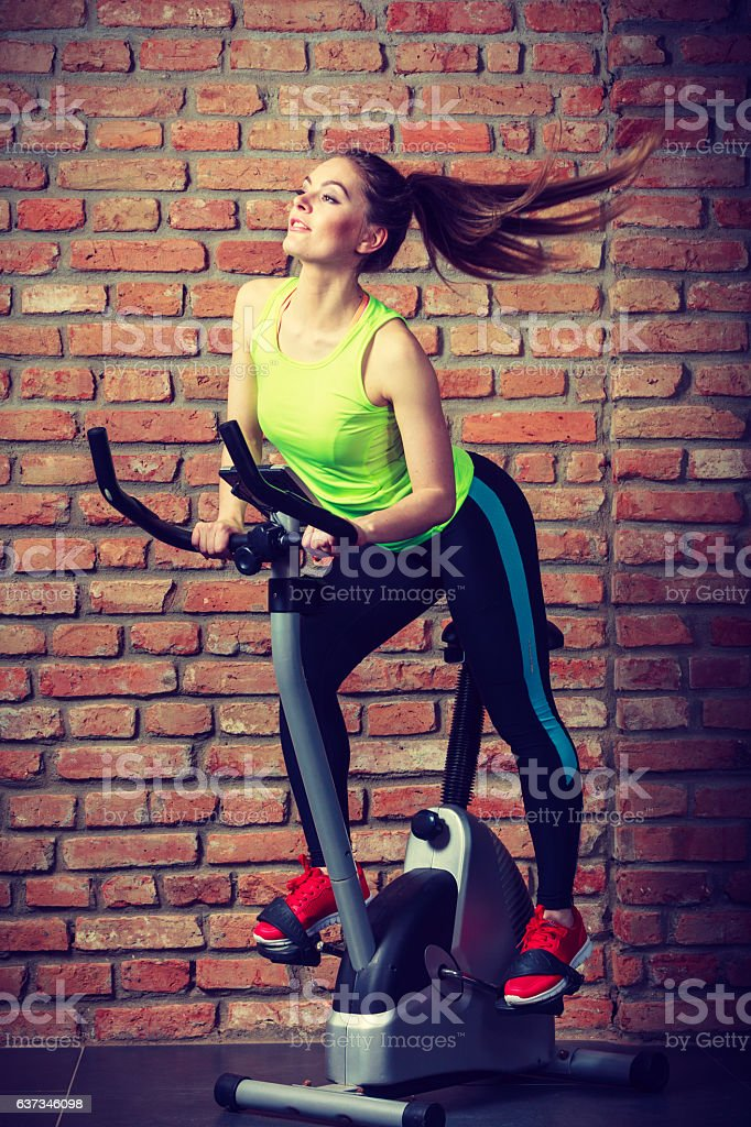 Active woman using exercise bike at the gym. stock photo