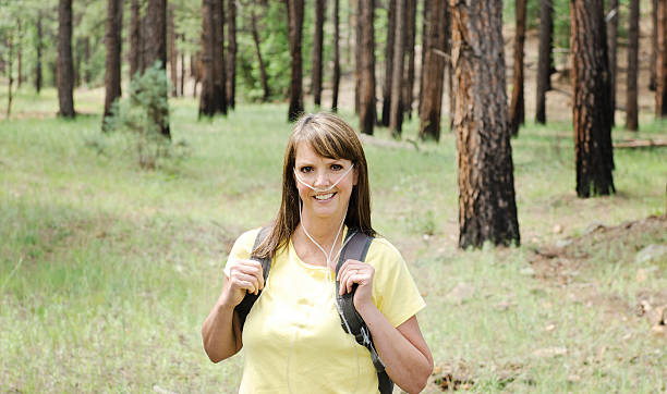 Active Woman Using Therapeutic Oxygen Middle aged woman with COPD hikes in the forest using portable oxygen therapy medical oxygen equipment stock pictures, royalty-free photos & images
