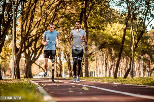 Active young sportsman running together with his disabled friend in a public park.