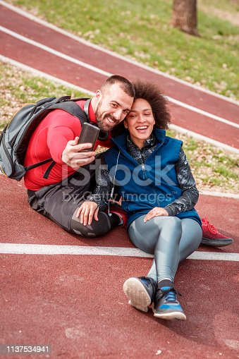 istock Active young couple sitting down on a running track in a public park and taking a selfie together 1137534941