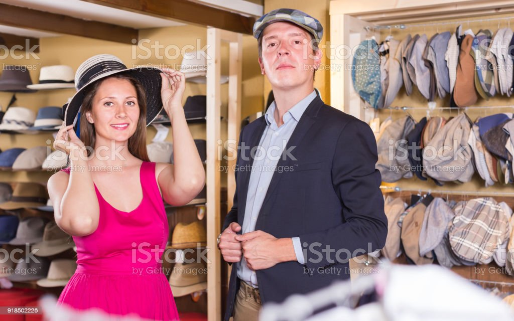 f06ef1b3 Active young female and man choosing hats in the store - Stock image .