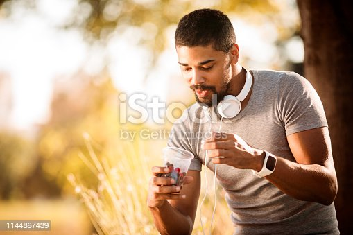Sporty young man eating berries from a plastic cup in a city park.
