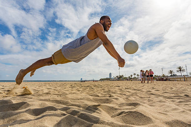 Active Young Man Jumping While Playing Beach Volleyball stock photo