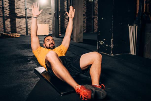 Aktive junge Sportler, die auf einer Trainingsmatte im Fitnessstudio ein Rückwärtsgymnastik-Training machen – Foto