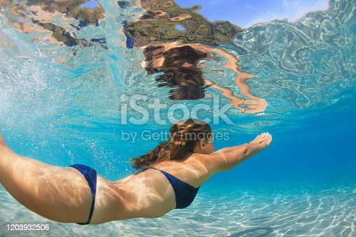 577645320 istock photo Active young woman swim underwater in tropical blue lagoon 1203932506