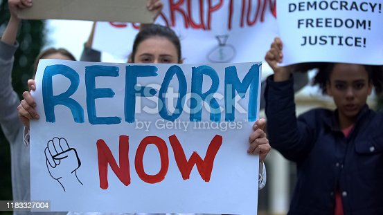 Activist showing banner Reform now, protesting corruption, unfair justice