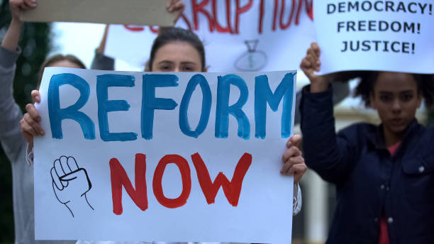 Activist showing banner Reform now, protesting corruption, unfair justice stock photo