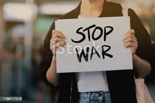 istock Activists raise anti-war message signs 1198117319