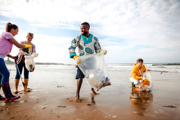 Activists Working Together Making a Difference Collecting rubbish off a beach. Plastic containers, bottles in their bag. They are using a mechanical grabber. Three women and a man working together environmental cleanup stock pictures, royalty-free photos & images