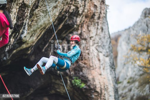 Two girls belaying from the cliff