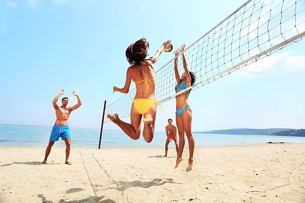 Activity on beach - group of friends playing volleyball stock photo