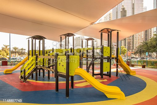 Shaded kid's playground activity tower (slides, climbing, ropes etc.)equipment at the Lake park in Abu Dhabi