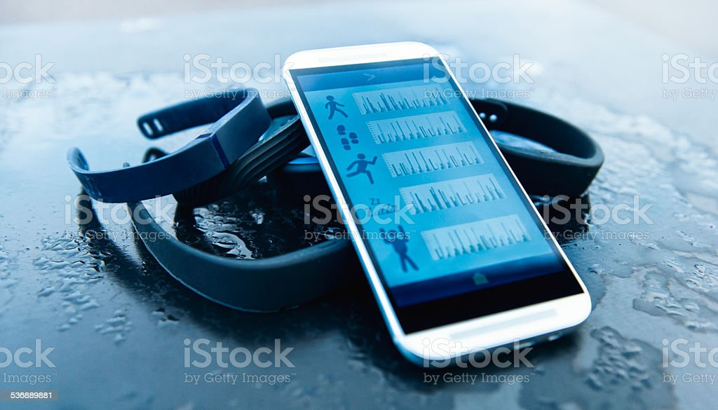 Activity trackers and mobile phone with app that shows data stock photo