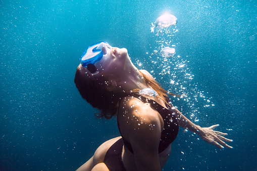 888067280 istock photo Activity woman with mask swimming underwater in sea, woman floats to the surface. 898936734