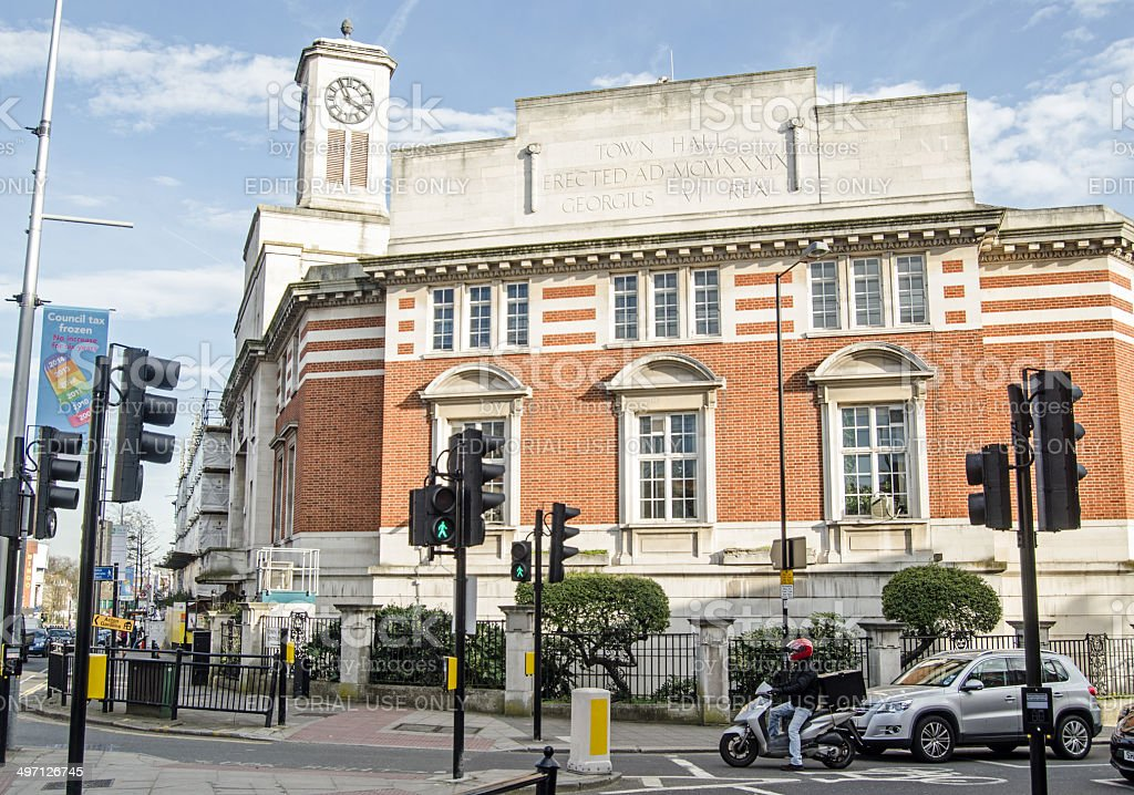 Acton Town Hall, West London London, England - March 15, 2014:  Acton Town Hall in the centre of the West London suburb with traffic waiting at a junction. Building Exterior Stock Photo