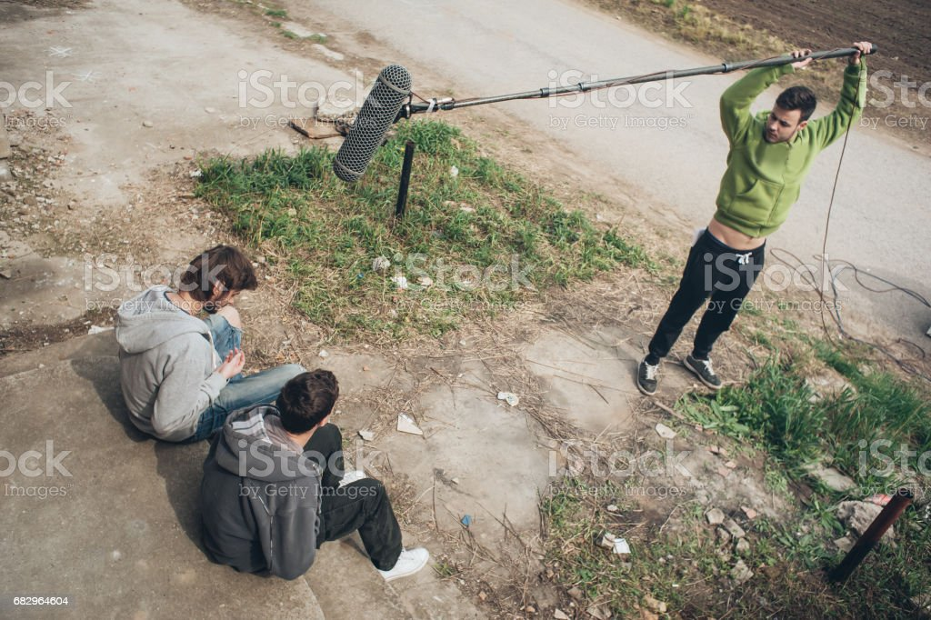 Actor behind scene. Sound boom operator hold microphone fisher outdoor stock photo