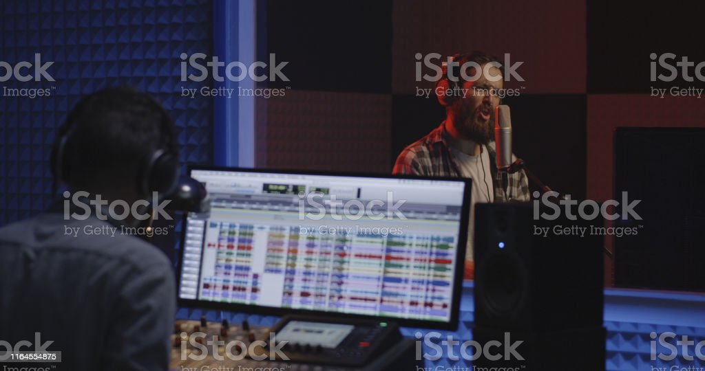 Medium shot of a male actor doing voice over in a sound studio