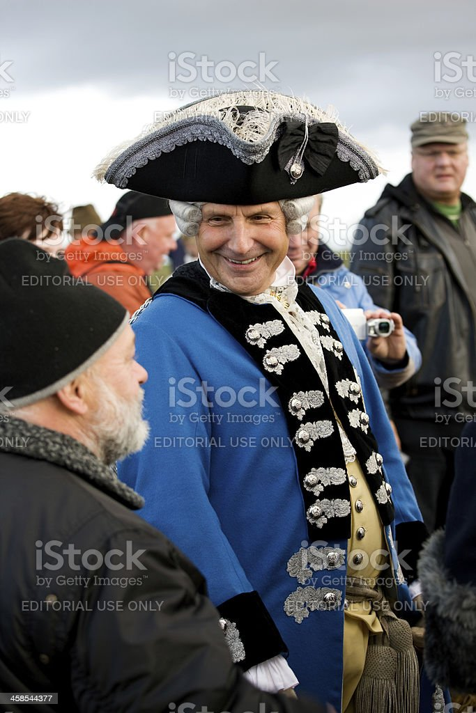 actor in historic costume talking to visitors stock photo