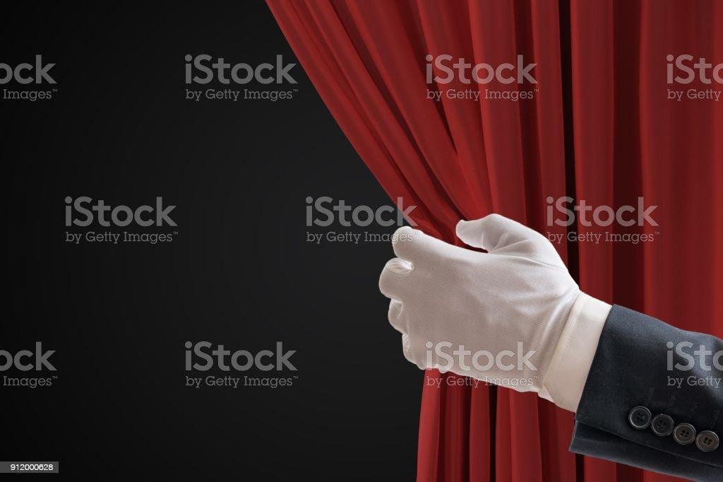 Actor is pulling red curtains in theatre with hand. stock photo