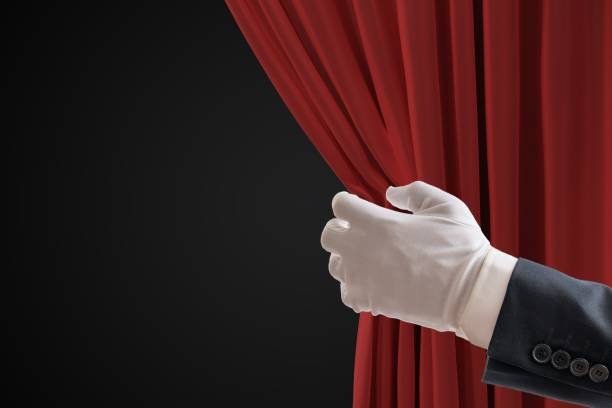 Actor is pulling red curtains in theatre with hand. - foto stock